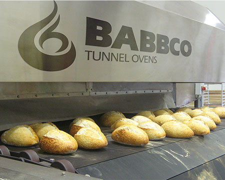 This is a photo of a BABBCO tunnel oven showing the BABBCO logo prominently displayed on the front of the oven.