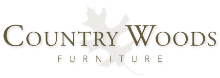 This is Country Woods Furniture's new logo.  The words Country Woods are in Adobe Garamond font over an illustration of an oak leaf in the background. The word furniture is at the bottom of the logo using the font Avenir at a smaller point size.